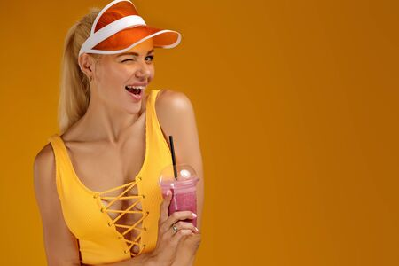 portrait of blonde girl in bathing suit and hat holding a fresh juice on orange background. healthy life. copy space
