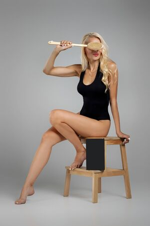 beautiful slim blonde woman in black bodysuit making a scrub massage with big brush. Cellulite treatment, dry brushing. box for spa cosmetic products Stock Photo