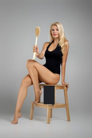 beautiful slim woman in black bodysuit making scrub massage with big wooden brush. Cellulite treatment, dry brushing. box for spa cosmetic products