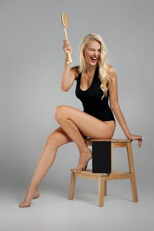 beautiful slim blonde woman in black bodysuit making a scrub massage with big wooden brush. Cellulite treatment, dry brushing. box for spa cosmetic products Foto de archivo - 130206797