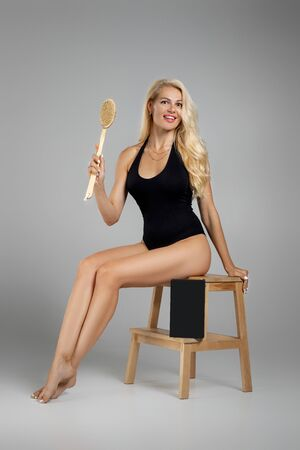 beautiful slim blonde woman in black bodysuit making a scrub massage with big brush. Cellulite treatment, dry brushing. box for spa cosmetic products