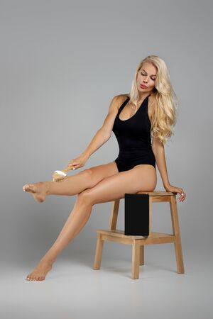 beautiful slim blonde woman in black bodysuit is massaging skin on her legs with big brush. box for spa cosmetic products on chair