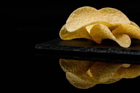 Salty delicious potato chips on board on black background