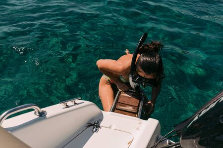 woman wearing a snorkel mask and climbs stairs in boat from a clear turquoise sea