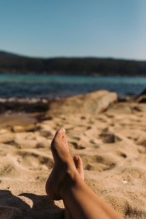 legs of a young woman lying on the beach on sunny summer day. Womans feet relaxing on the beach.