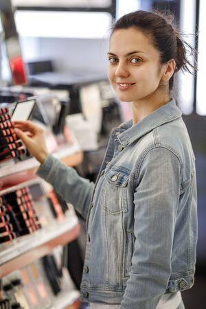 Woman customer testing lipstick in make-up shop. Choosing lipstick from shelf and selection. Using tester. Фото со стока