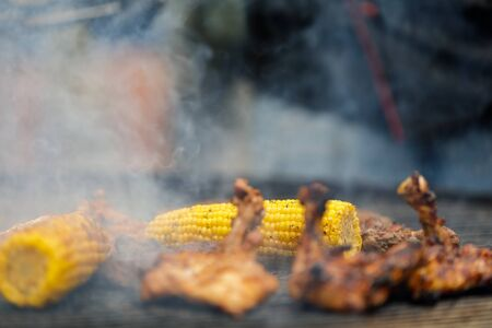 Process of grilling corn cobs, chicken legs and shrimp