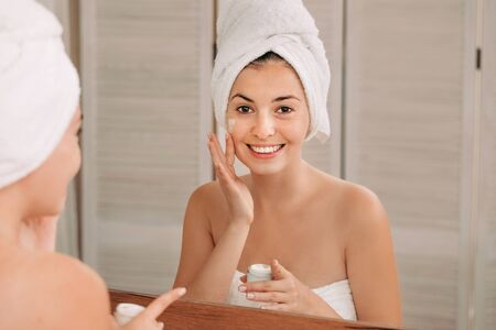 Portrait of beautiful woman caring of her skin. girl looking at mirror and applying cream on her face in front of the mirror in bathroom