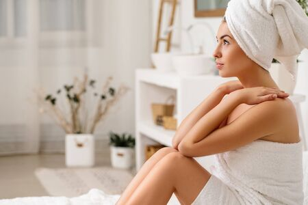beautiful young woman wrapped in a shower towel sitting on bed. copy space Reklamní fotografie