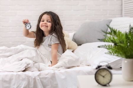 cute smiling little child girl in pyjamas with clock in bed. good morning