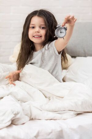 cute smiling little child girl in pyjamas with clock in bed. good morning 写真素材 - 131716663