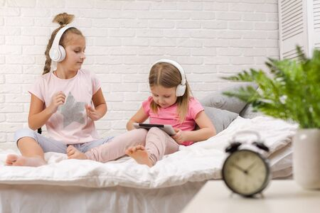 two cute children girls playing in the bedroom. two cute children girls use digital tablet in bed.
