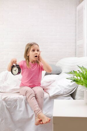 cute surprised little child girl in pyjamas with clock in bed. good morning Фото со стока