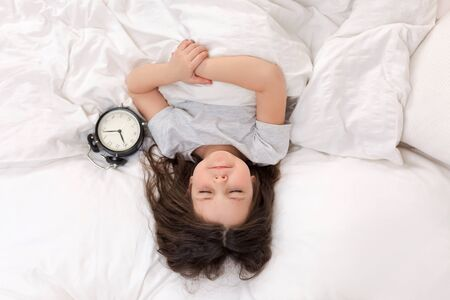 cute little child girl in pyjamas with clock in bed. good morning. top view 写真素材