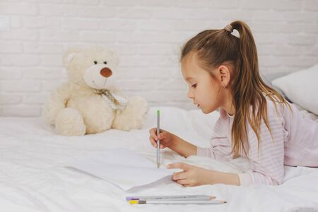 cute little girl drawing pictures while lying on bed. Kid painting at home Stok Fotoğraf