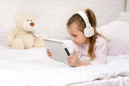 cute little child girl lies in bed uses digital tablet. child playing on tablet pc. Stock Photo