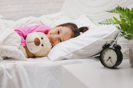 Cute happy little child girl sleeping with teddy bear in her bed Stock Photo