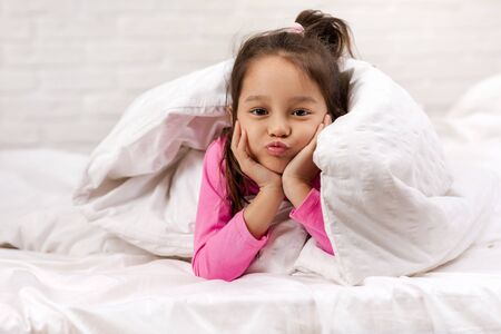 happy morning baby in bed. child dabbles in bed Stock Photo