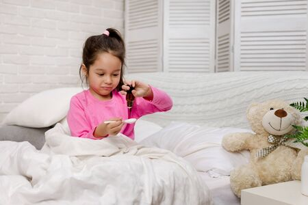 Sick little child girl pouring antipyretic syrup for kid in bed Stock Photo