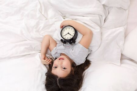 cute little child girl in pyjamas with clock in bed. good morning. top view Stockfoto