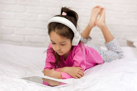 cute little child girl lies in bed uses digital tablet. child playing on tablet pc. Banco de Imagens