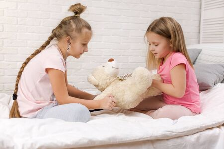 two cute children girls playing doctor with teddy bear at home. girl listens a stethoscope to toy.