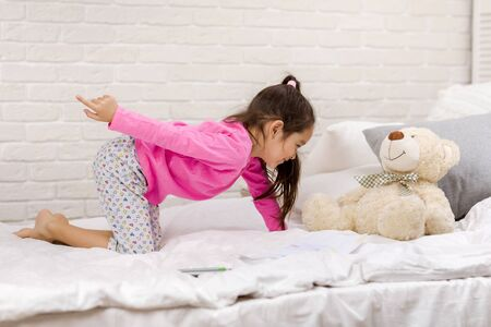 adorable little multinational child girl playing with teddy bear in bed in morning