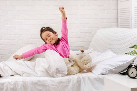 cute little child girl wakes up from sleep and yawns in bed in the morning 写真素材 - 131857892