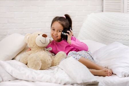 cute little child girl in pyjamas with clock in bed. good morning 写真素材 - 131857769