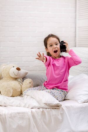 Surprised cute little child girl in pyjamas with clock in bed. good morning 写真素材 - 131857684