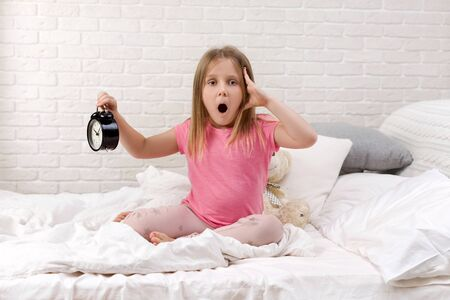 cute surprised little child girl in pyjamas with clock in bed. good morning 写真素材 - 132220295