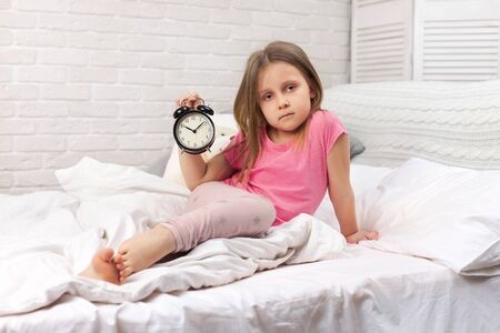 tired sleepy little child girl in pyjamas with clock in bed. good morning