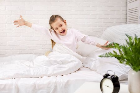 cute little child girl wakes up from sleep in bed in the morning 写真素材 - 131857777