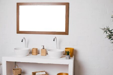 bathroom with two sinks. big mirror hanging on white wall.