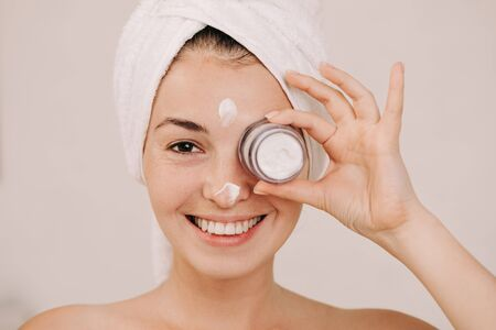 Portrait of beautiful woman in towel holding jar of face cream Banco de Imagens