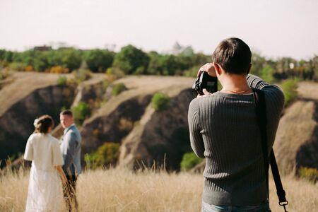 El fotógrafo de bodas toma fotografías de los novios en la naturaleza en otoño, el fotógrafo en acción.
