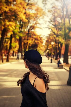 fashionable curly woman in black hat walking on the street on the background of colorful autumn leaves. rirl look back . Back view