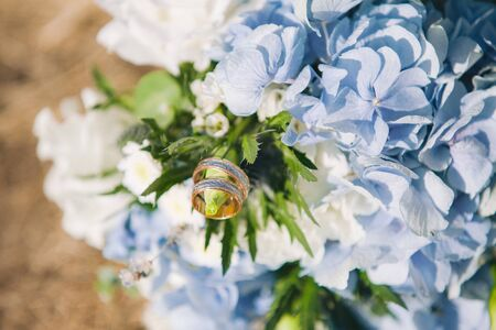gold wedding rings on bouquet with beautiful hydrangea