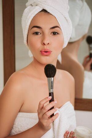 Retrato de mujer hermosa morena aplicar maquillaje en la cara después de una ducha en casa. niña sopla el exceso de polvo de un cepillo Foto de archivo