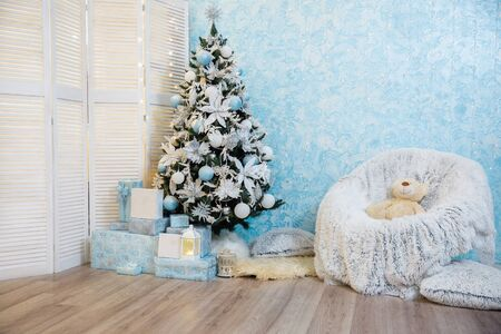 Christmas tree decorated with lights garland. photo studio. Christmas and New Year gifts. room with christmas interior