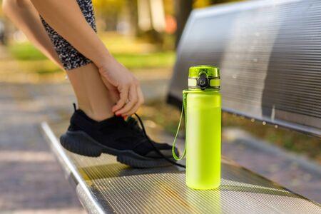 bouteille d'eau sur le banc. coureur attachant ses chaussures sur fond. Banque d'images