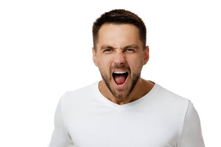portrait of furious enraged bearded man in casual white shirt shouting and screaming isolated on white background