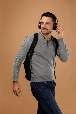 handsome young man in headphones with backpack listens to music isolated on beige background.