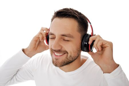 Close-up portrait of handsome young man in headphones listening to music and dancing isolated on white background. 스톡 콘텐츠
