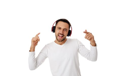 handsome smiling young man in headphones listening to music, dancing and singing isolated on white background.