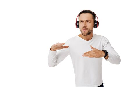handsome young man in headphones listening to music and dancing isolated on white background.
