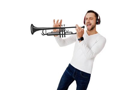 handsome young man in headphones listening to music and playing an imaginary musical trumpet isolated on white background.