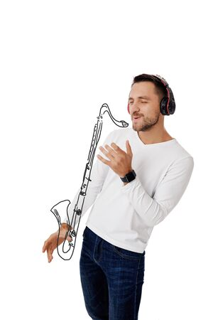handsome young man in headphones listening to music and playing an imaginary saxophone isolated on white background.