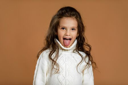 happy funny little child girl in white sweater showing her tongue on beige background. facial expression Фото со стока