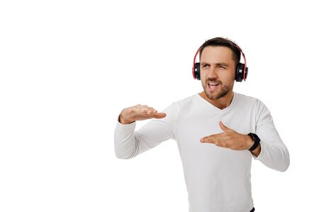 handsome young bearded man in headphones listening to music and dancing isolated on white background. 스톡 콘텐츠